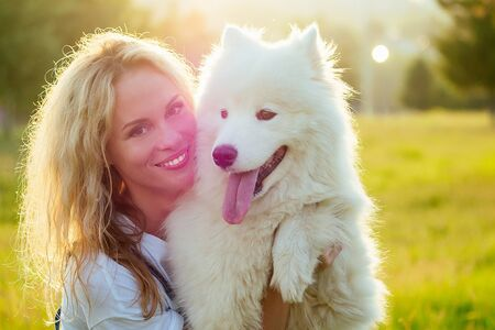beautiful and charming curly blonde smiling toothy woman in denim overalls are sitting at glass kissing a white fluffy samoyed dog in the summer park sunset rays background 写真素材 - 132900575