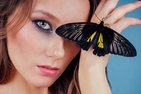 Art photo fashion model shows a bright make-up. Beautiful young sexy woman green eyes and live butterfly yellow black wings.sensual close-up portrait perfect skin, professional makeup and hairstyle