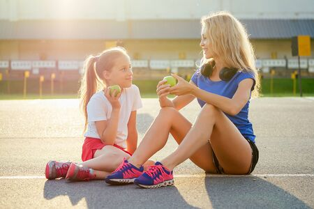 young and beautiful blonde woman together with a little girl in sportswear sitting on the asphalt and eat a green apple at the stadium. Active family mother and daughter jogging in the summer morning