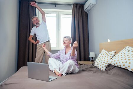 blonde short haircut woman meditating with laptop yoga video teacher in nightwear and elderly man doing stretching hands,spine in day light bedroom apartment Foto de archivo
