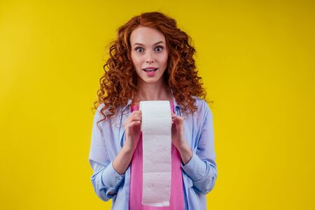 Beautiful curly redhead ginger woman holding toilet paper roll on yellow color background 写真素材