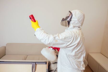 pest control worker in uniform spraying pesticides under couch in living lounge room Foto de archivo