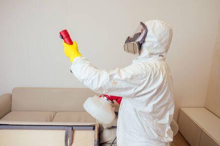 Trabajador de control de plagas en uniforme de fumigación de pesticidas debajo del sofá en el salón Foto de archivo