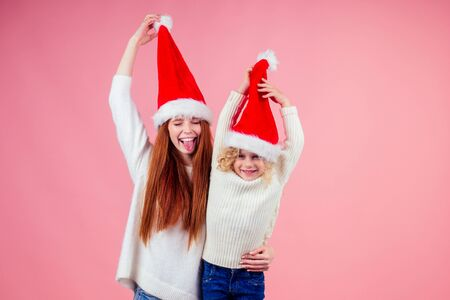 ,happy redhead ginger woman and cute little blonde girl hiding eyes under santa claus hat and having fun together in studio pink background