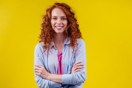 redhaired ginger woman with curly red hair having fun in studio yellow background