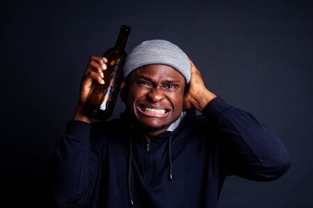 african american man holding a bottle of wine and feeling headache shit in studio black background.bum homeless drowning out the pain 写真素材
