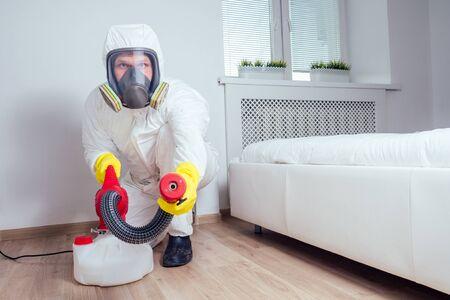 addetto al controllo dei parassiti sdraiato sul pavimento e spruzzando pesticidi in camera da letto