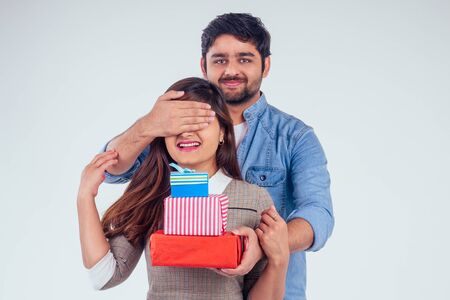 beautiful indian woman and handsome turkey man giving gift boxes in studio white background.New year or Ekadashi concept Stockfoto