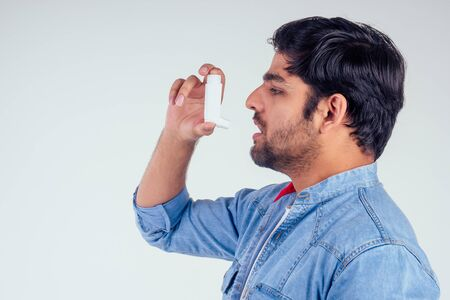 Young indian man in a denim jeans jacket using asthma inhaler at studio white background 写真素材