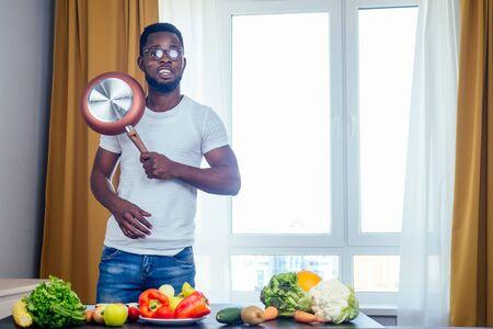 afro male hamds cutting apple,eggplant and kivi