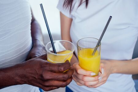 international couple in love holding in hands glasses with orange juice.afro man use disposable tableware,but european woman useing eco steel tubes