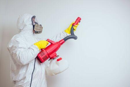 Trabajador de control de plagas rociar pesticidas con pulverizador en apartamento copia spase paredes blancas antecedentes Foto de archivo