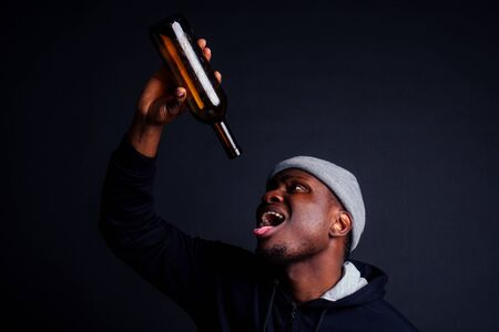 african american gue wearing gray hat and hoody hjlding botle with wine in srudio black background.alcoholism homeless bum concept