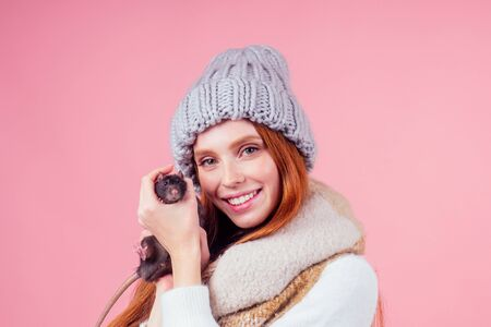 happy beautiful redhaired ginger good-loking woman wearing trendy knitted hat with sweater holding her lovely black male rat in studio pink background Stock Photo