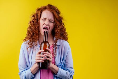 curly redhead ginger woman drinking beer and feeling bad mood in csudio yellow background