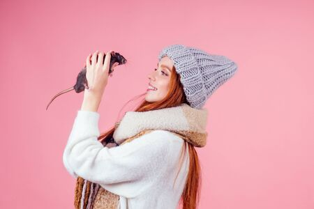 redhaired ginger girl in knitted hat and warm scarf hugging cute black male rat in studio gray background.two thousand and twentieth year symbol Stock fotó
