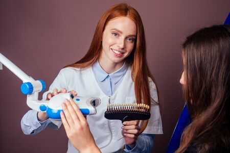 dentist matching teeth color of beautuful red haired ginger woman with palette in clinic, teeth whitening concept