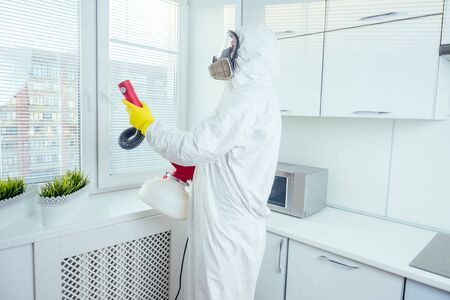 white worker spraying pesticide on induction hob Archivio Fotografico