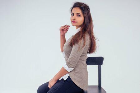 Hermosa mujer india con camisa blanca con cuello y suéter con cabello negro castaño en el estudio de fondo blanco.