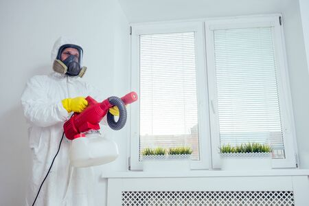 Baby room cleaning .Worker spraying insecticide in bedroom Banque d'images - 133688216