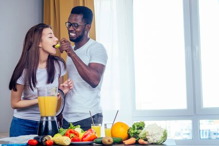 african american man with asian woman making smoothie at home, useing eco tubes from metall