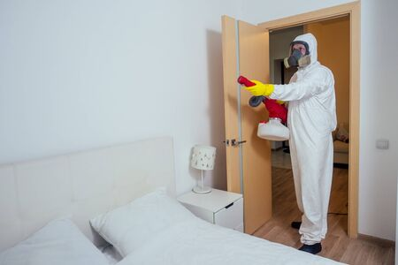 Baby room cleaning .Worker spraying insecticide in bedroom Banque d'images - 133688346