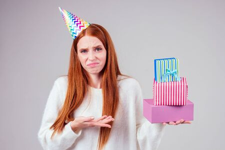 disappointment redhaired ginger woman dissatisfied sad grimace wearing birthday cap horn holding many gift boxes in studio white background. she do not like celebrating aging