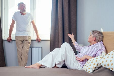 blonde shorh haircut woman quarreling with her elderly husband in day light bedroom.handsome man standing at the windowsill and looking at wife