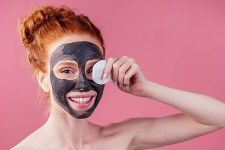 redhaired ginger teenager girl with black clay mask on her pretty face on pink studio background .