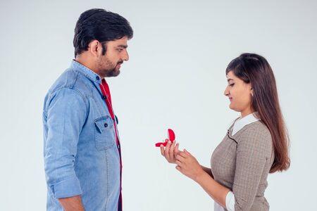 bold indian woman asking her boyfriend to get wedding studio white background