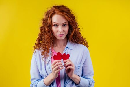 Sad redhaired ginger curly cry female tearing up red broken paper heart in studio yellow background..sex education 写真素材