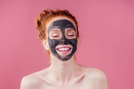 redhaired ginger teenager girl with black clay mask on her pretty face on pink studio background Stock Photo