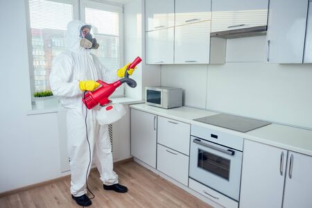white worker spraying pesticide on induction hob Banque d'images - 133688788