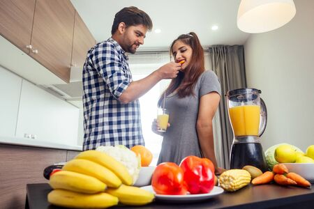 happy indian woman and handsome man mixing fruits for fresh smoothie in bright day light cozy kitchen