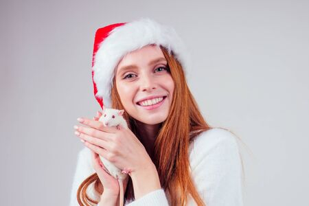 redhaired ginger girl in red santa hat hugging cute rat in studio gray background.two thousand and twentieth year symbol of good luck and wealth