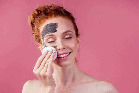 redhaired ginger teenager girl remove with cotton black clay mask on her pretty face on pink studio background