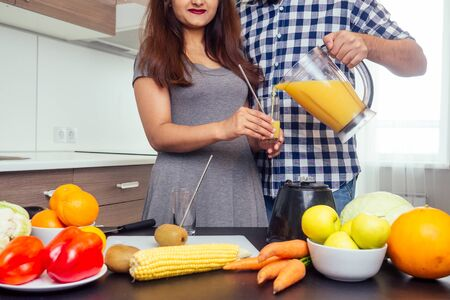 healthy and eco lifestyle.happy indian woman with her husband making smoothie in big kitchen. Stock Photo