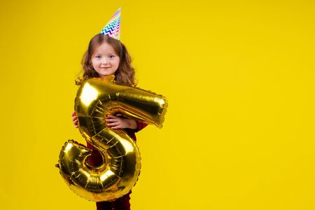 cute little girl surprised and amazed with birthday cap horn holding ballons 5 years anniversary numeral and gift box in studio white background Stock Photo