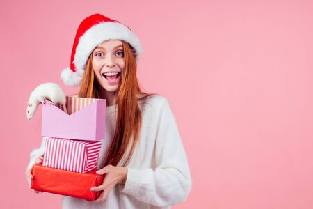 amazed and surprised redhaired ginger girl in red santa hat holding a bunch of gifts boxes and cute rat in studio gray background.two thousand and twentieth year symbol