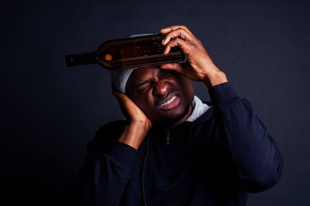 african american man holding a bottle of wine and feeling headache in studio black background.bum homeless drowning out the pain