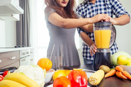 healthy and eco lifestyle.happy indian woman with her husband making smoothie in big kitchen