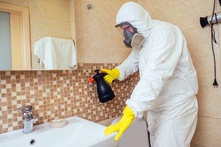 pest control worker spraying pesticides with sprayer in bathroom:processing the toilet and shower Banque d'images - 133688936