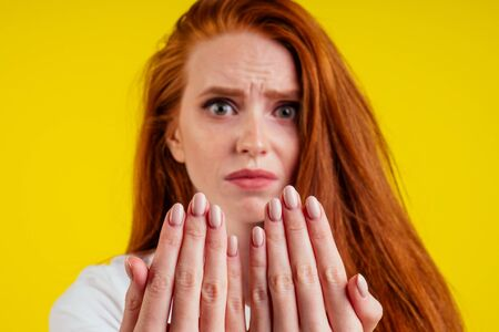 close-up portrait of nervous unhappy young redhaired ginger woman looking at a broken fingernail and crying .nude manicure in studio yellow background.dry and split ends of hair 写真素材