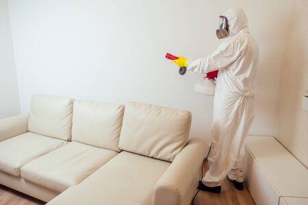 Trabajador de control de plagas en uniforme rociando pesticidas debajo del sofá en la sala de estar.