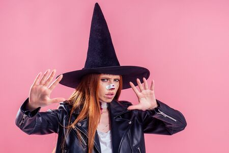 sad redhaired ginger woman witch black hat and in leather jacket holding out hands in front of herself with crazy make up on pretty face in studio pink background.stop to scaring me