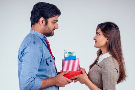 beautiful indian woman and handsome turkey man giving gift boxes in studio white background.New year or Ekadashi deepawali concept