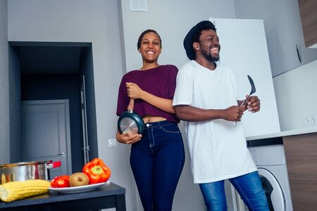 Beautiful young Afro American couple is smiling while dancing in kitchen