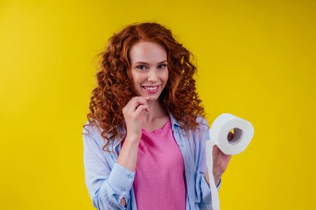 redhaired curls ginger female with hygiene paper on studio yellow background
