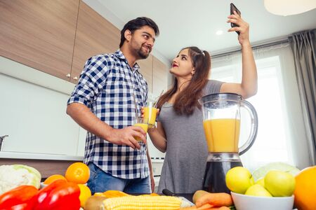 healthy and eco lifestyle.happy indian woman with her husband making smoothie in big kitchen,taking photos portrait on smartphone camera Stok Fotoğraf