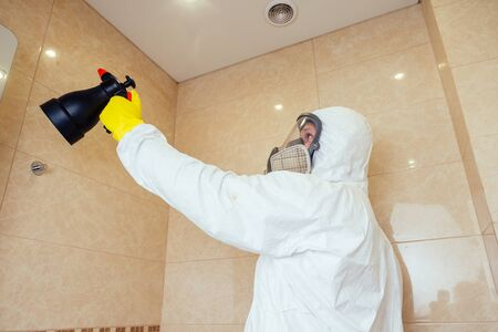 pest control worker spraying pesticides with sprayer in bathroom:processing the toilet and shower Banque d'images - 133689114